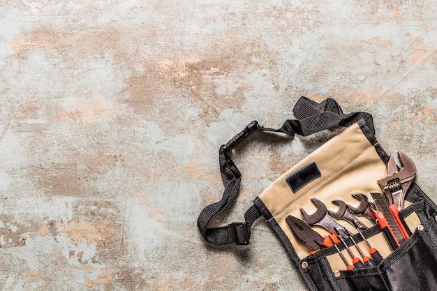 Vista dell'angolo alto di vari strumenti in toolbag su vecchio fondo di legno