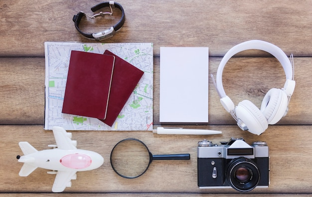 High angle view of various traveler accessories on wooden backdrop