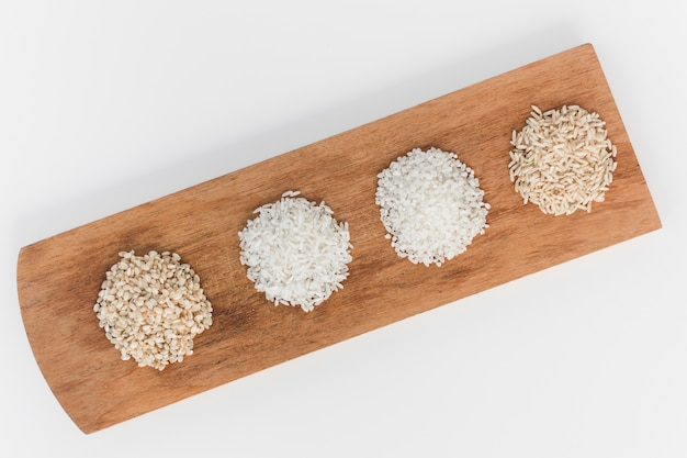 High angle view of various uncooked rice on wooden tray