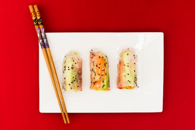 High angle view of vegetable rice spring rolls decorated with sesame seeds on white plate with wooden chopsticks