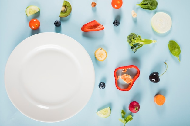 High angle view of vegetables and plate on blue background