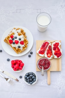 High angle view of waffles with berry fruits and milk