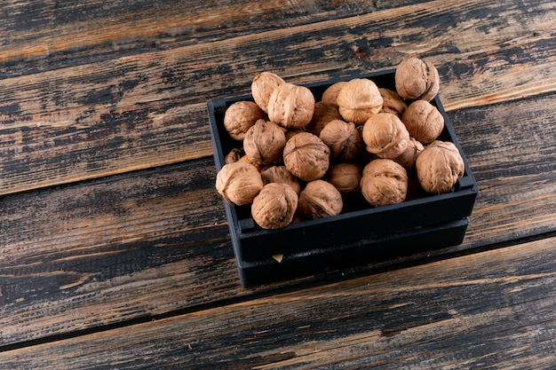 High angle view walnuts in black box on wooden horizontal