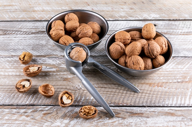 High angle view walnuts in bowls with nutcracker on wooden horizontal