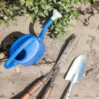 High angle view of watering can; hand shovel and gardening scissors near green leaves