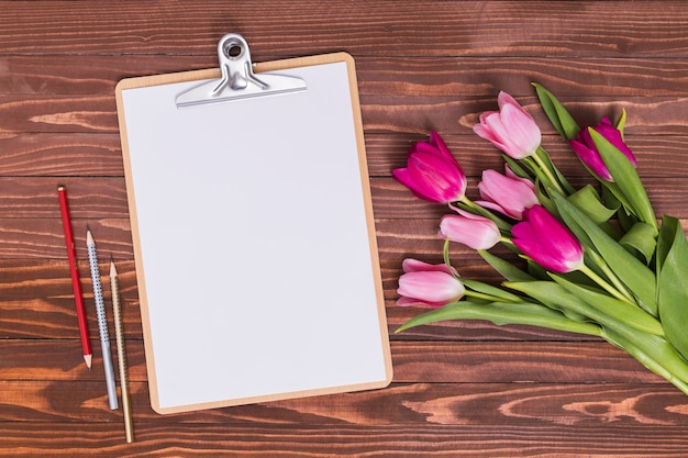 High angle view of white blank paper; pencils; clipboard with pink tulip flowers against wooden backdrop