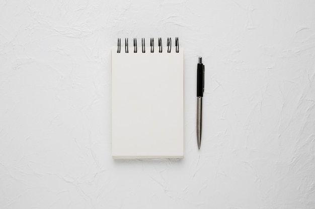High angle view of a white blank spiral notepad with ballpoint pen