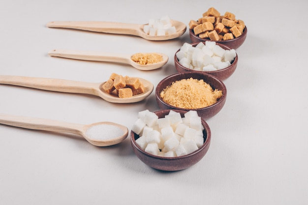 High angle view white and brown sugar in bowls with spoons