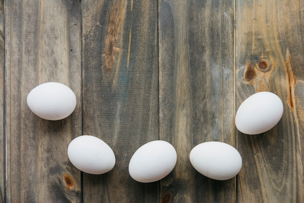 High angle view of white eggs on wooden background