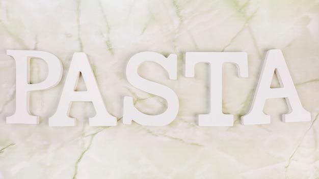 Vista dell'angolo alto della parola bianca della pasta su marmo