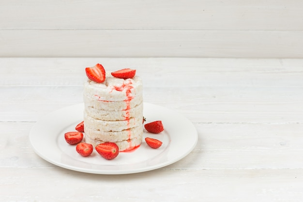 白い木の板の表面にイチゴとプレート上の高角度ビュー白いお餅。