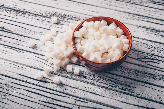 High angle view white sugar cubes in bowl on white wooden table. horizontal