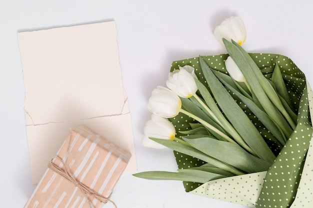 High angle view of white tulip flowers bouquet; gift box with blank paper on white background