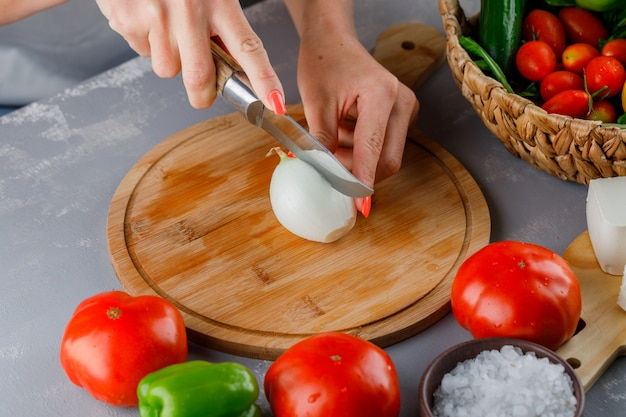 High angle view woman cutting onion into half on cutting board with knife, green pepper, cucumber, salt on gray surface