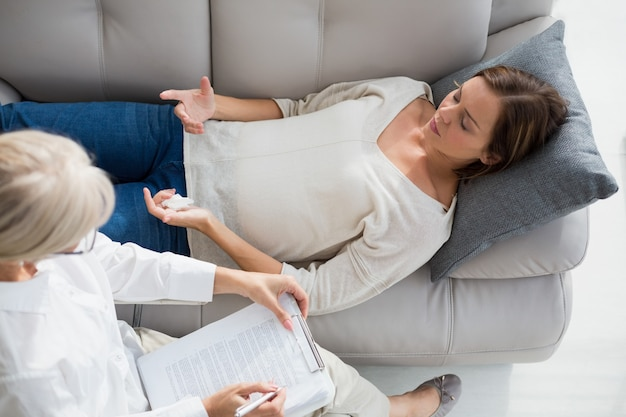 High angle view of woman lying on sofa by therapist