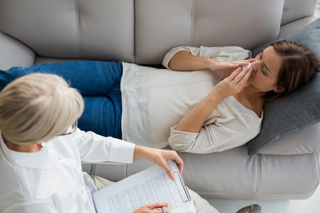 High angle view of woman relaxing on sofa by therapist