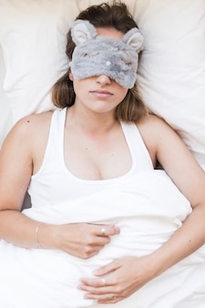 High angle view of a woman sleeping with an eye mask