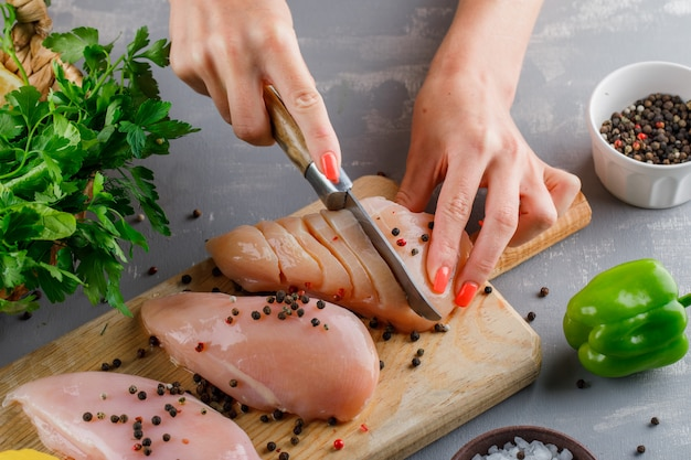High angle view woman slicing chicken breast on cutting board with pepper, green pepper on gray surface