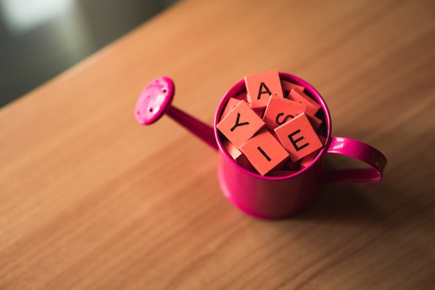 High angle view of wooden alphabet in watering can on desk