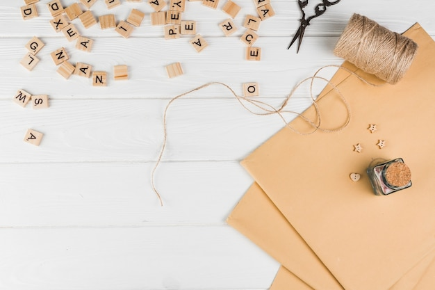 High angle view of wooden text cube; string spool scissor with brown paper on white table