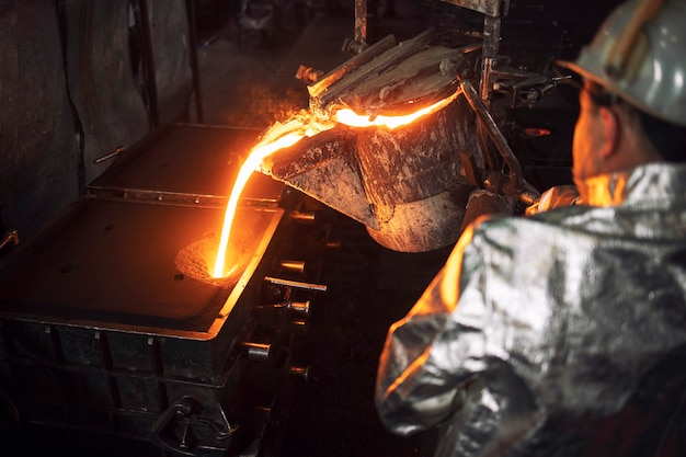 High angle view of worker filling casting molds with hot molten iron, steel production and metallurgy.