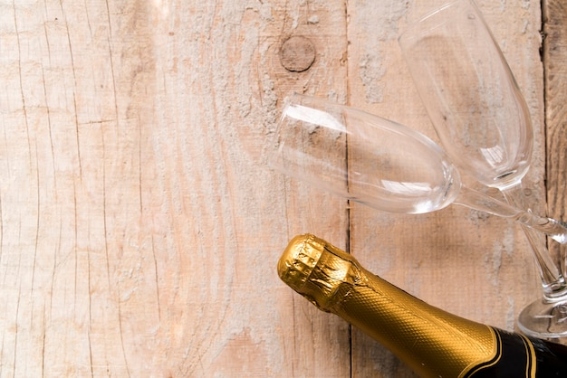 High angle view of wrap champagne bottle and empty glasses on wooden surface