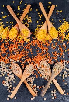 黒い石のテーブルに木製のスプーンで黄色と緑のレンズ豆をハイアングル。垂直