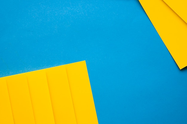 High angle view of yellow cardboard papers on blue backdrop