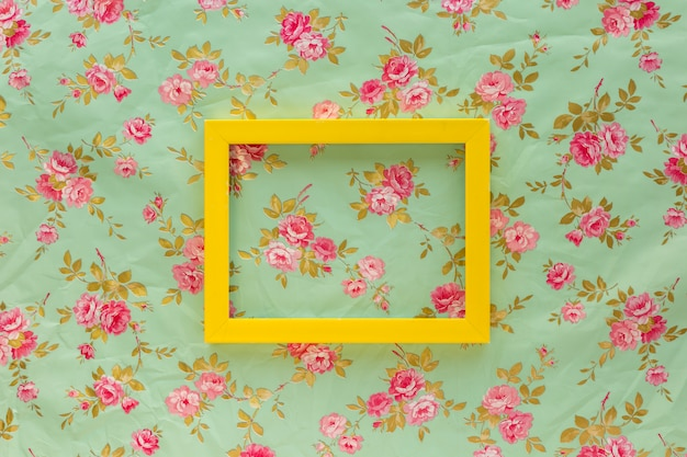 High angle view of yellow empty frame against floral print background