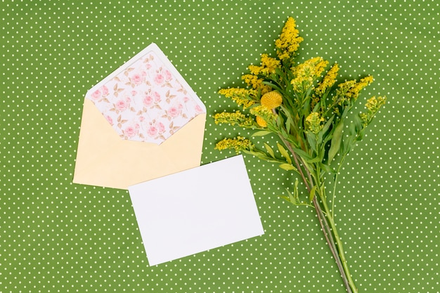 High angle view of yellow goldenrod flowers with card; open envelope above green textured background