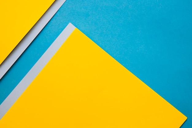 Vista dell'angolo alto delle carte del cartone giallo e grigio sul contesto blu