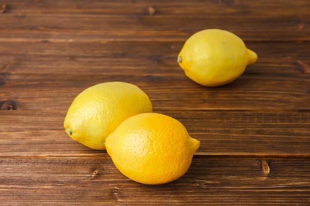 나무 표면에 높은 각도보기 노란색 레몬. 텍스트의 가로 공간