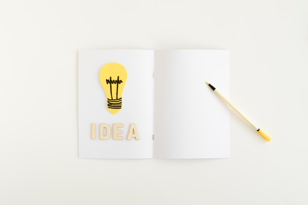 High angle view of yellow light bulb with idea text on white card