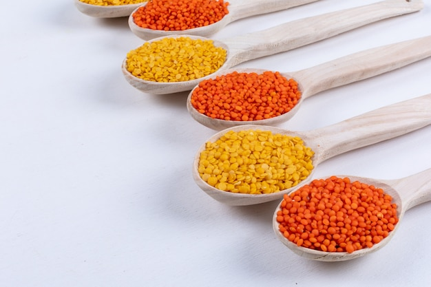 High angle view yellow and red lentils in wooden spoons