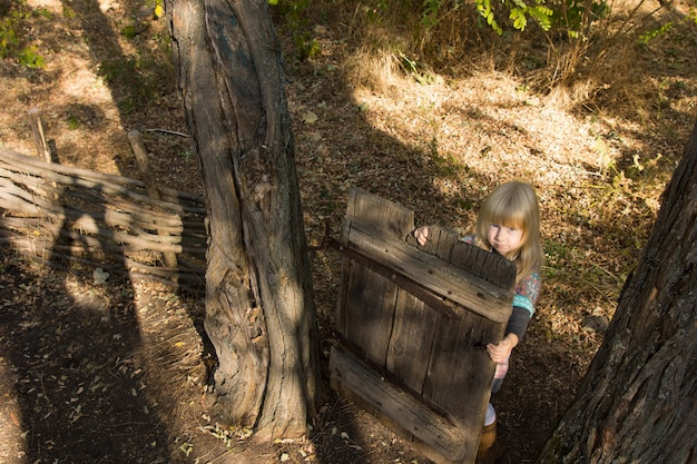 High angle view of a young blond girl playing with an old wooden gate between two trees in a garden looking up at the camera