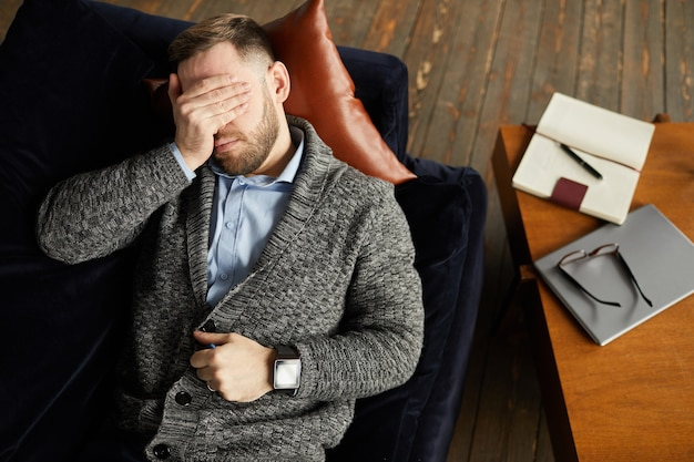 High angle view of young businessman lying on the sofa and closed his eyes with hand he tired of work