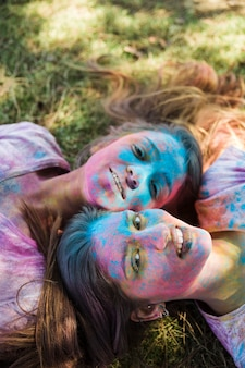 High angle view of young women with holi color on their face lying on lawn looking at camera
