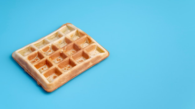 High angle of waffle on blue background with copy space