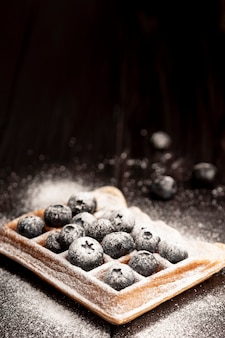 High angle of waffle with blueberries covered in powdered sugar