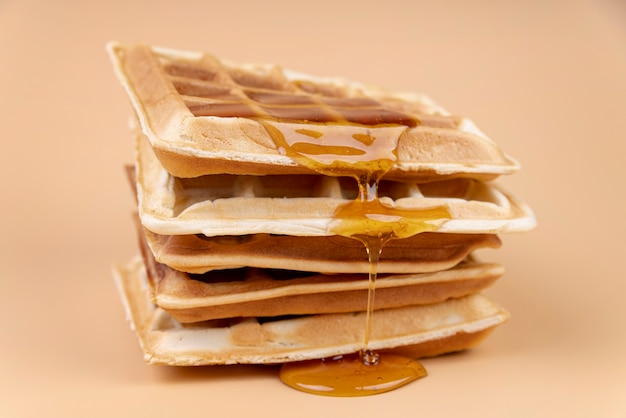 High angle of waffle with dripping honey