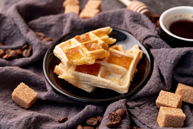 High angle of waffles covered in honey on plate with sugar cubes