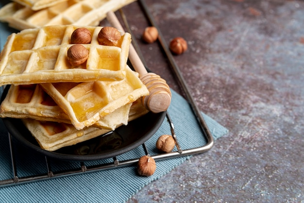 High angle of waffles on plate with hazelnuts and honey dipper