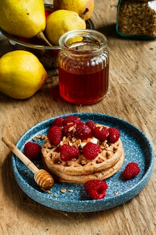 High angle waffles with raspberries and honey