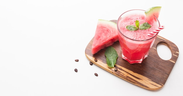 High angle of watermelon cocktail glass on chopping board with copy space