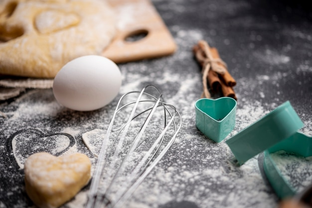 High angle of whisk and egg with dough for valentines day