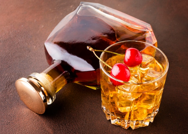 High angle whiskey glass and cherries with bottle