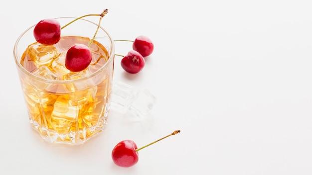 Bicchiere da whisky ad alto angolo e ciliegie con copia-spazio