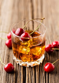 High angle whiskey glass with ice and cherries