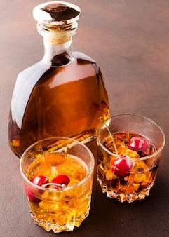 Whisky ad alto angolo sulle rocce con ciliegie e bottiglia