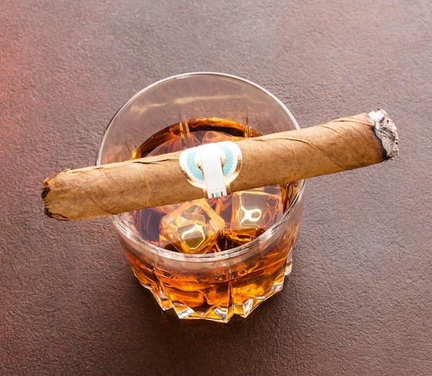 Виски под высоким углом со льдом и сигарой